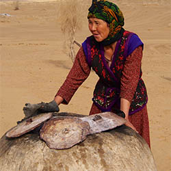Karakum Desert - baking churek Turkmen bread in a tandyr clay oven